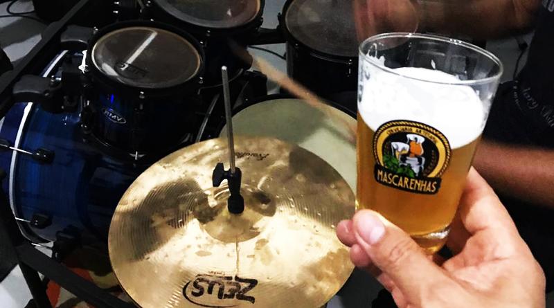 bateria com músico e copo de cerveja